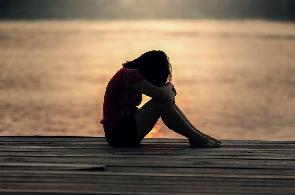湖のほとりで悲しむ女
