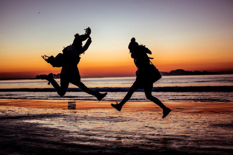 海辺で飛び跳ねる2人